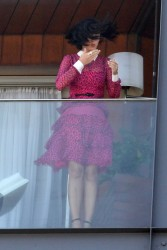 Katy Perry in a pink leopard print dress waves from her windy Balcony in Rio 7/30/12